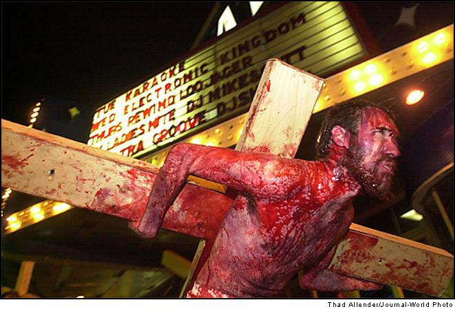 brutal depiction of blood-streaked man carrying cross